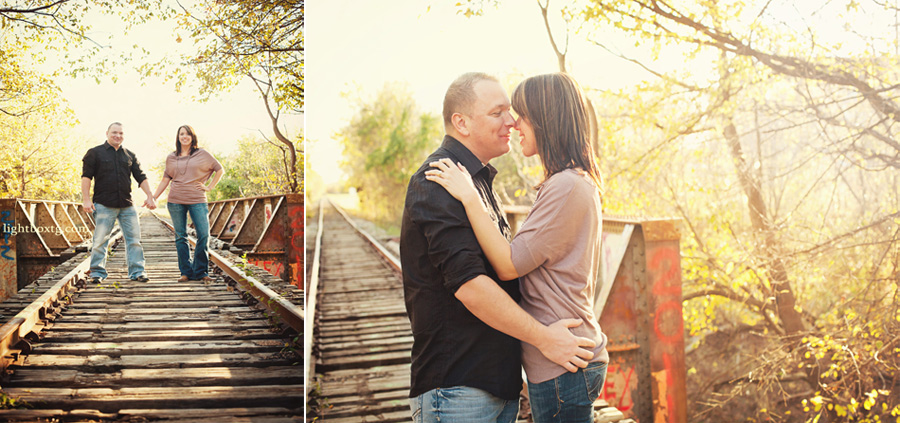 couple holding hands and laughing during engagement session at an abandoned railroad track in Allen TX