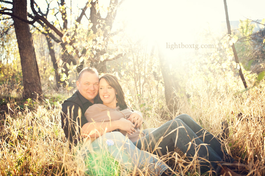 couple in love sitting in tall field of grass with sun flare in background among trees at abondoned railroad in Allen TX with a vintage rustic inspiration